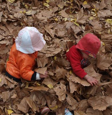 枯葉に埋もれる二人の子ども