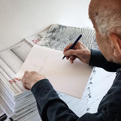 Dani Karavan signiert Kataloge mit Widmung für die Ausstellungsbesucher.