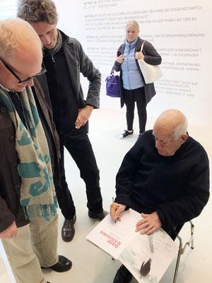 Dani Karavan signiert einen Katalog für Jürgen Bisch, daneben Christian Höhn, der Fotograf