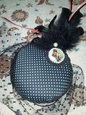 Tocado de lunares, adornado con plumas, pasamanería de seda negra y camafeo. Velo de plumeti.