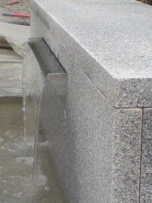 Detail eines Wasserspeiers in einer Granitwand