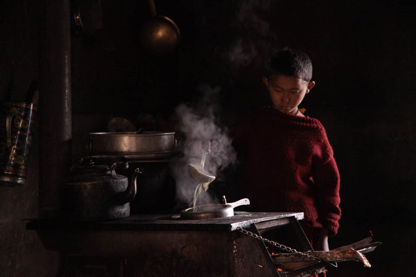 Young monk making yak tea, Tsum Valley
