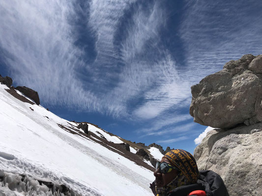 Beautiful cloud formations above us while taking a break at a giant boulder below camp 2