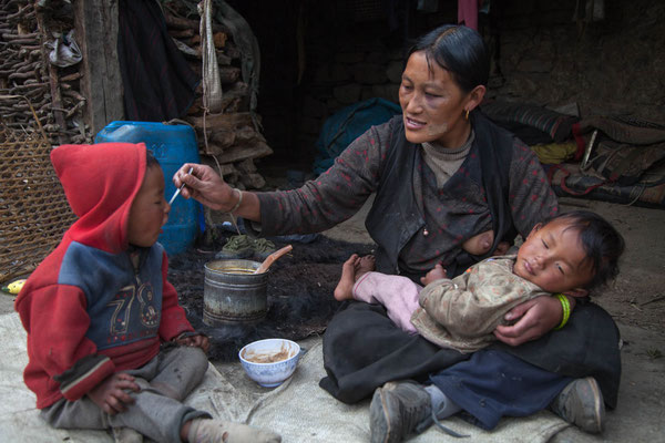 A mother feeding her children in the Manaslu region