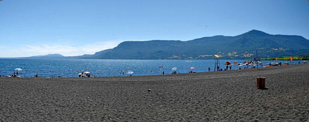 Pucon hat einen sehr schönen schwarzen Lavasand-Strand am See, riesenlang.