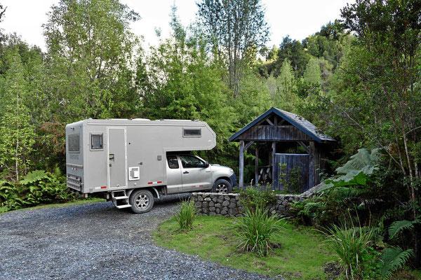 Typischer Campingplatz im Pumalinpark. Wegen des vielen Regens haben Tisch und Bänke ein Dach über sich.