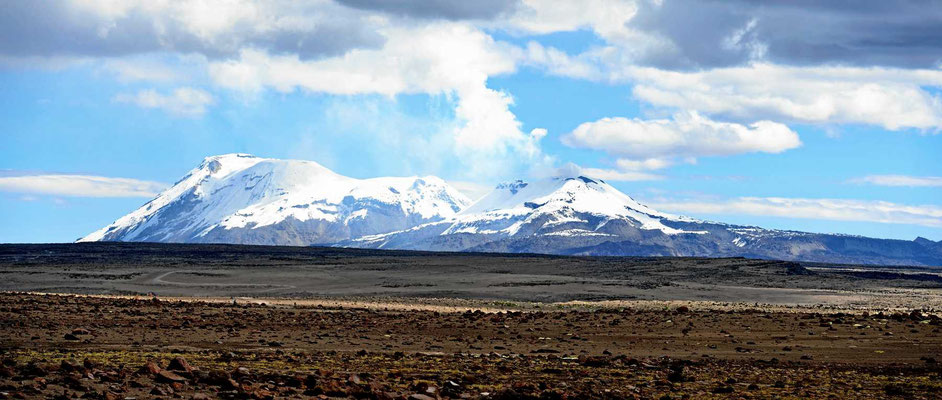 Ein Pass auf 4800 m, Rückblick auf den Berg Corupana (6613 m) und einen rauch spukenden Vulkan rechts daneben