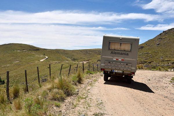 Der Weg windet sich durch eine weite, kahle Landschaft.