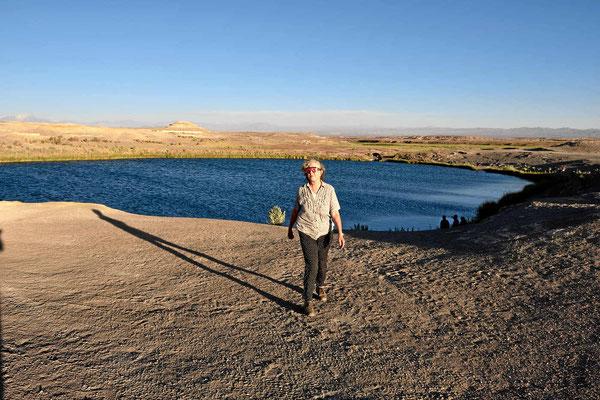 Ein kleiner kreisrunder See mitten in der vegetationslosen Wüste.