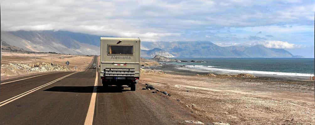Von Iquique aus geht es die Küste entlang. Eine kleine Küstenebene und dahinter hohe Berge und alles kanlltrocken.