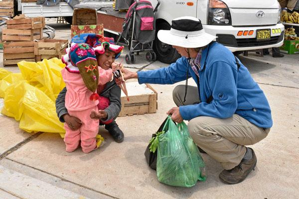 Markt am Titicacasee.  Marion spielt mit einem Kind mitsamt Barbiepuppe.