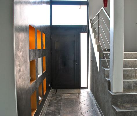 Entrée traitée avec enduit décoratif noir et niches éclairée.