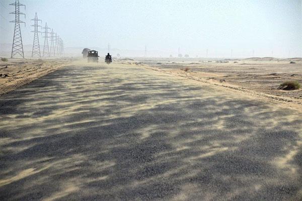 Die Eskorte fährt uns durch die Sandverwehungen davon