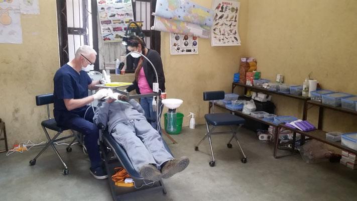 """Zahnarzt Gerd Korves/Lingen in seiner provisorisch aufgebauten """"Camp-Praxis"""" beim Behandeln - mit mobiler Einheit und portablem Behandlungsstuhl"""