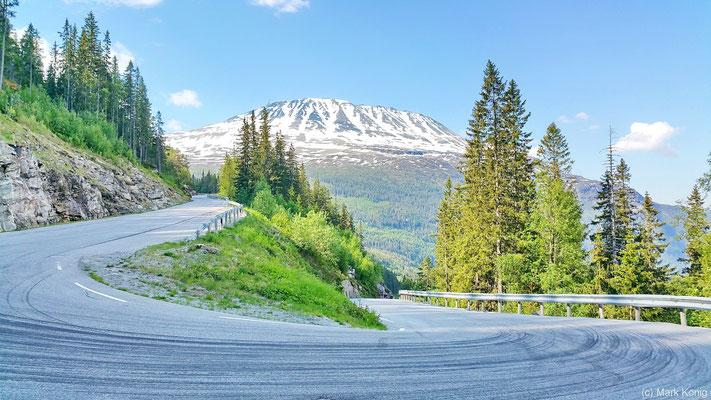 Aufnahme des Schnee bedeckten Bergs Gaustatoppen aus einer Haarnadel-Kurve der Pass-Straße (Rv651)