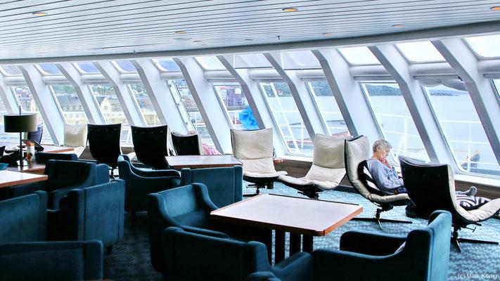"""Die Panoramalounge der """"MS Kong Harald"""" bietet komfortable Sitzgelegenheiten und Ausblick nach vorn und zu beiden Seiten des Postschiffs"""