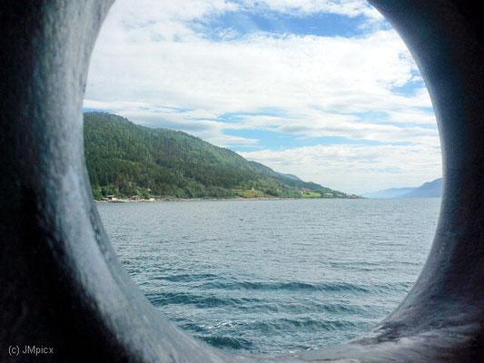 Bei Fährfahrten über einen Fjord lohnt sich manchmal der Blick oder das Foto durchs Bullauge (hier: Sølsnes - Åfarnes)