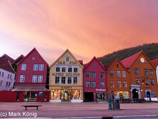 Weltkulturerbe: Das historische Hanseviertel Bryggen in der Stadt Bergen vor orangefarbenem Abendhimmel