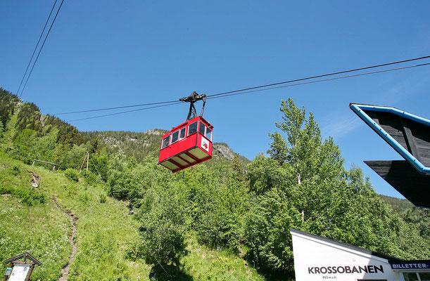 """Die rote Kabine der Seilbahn """"Krossobanen"""" in Rjukan vor blauem Himmel und grünem Wald (bearbeitete Aufnahme, Original: Trond Strandsberg)"""