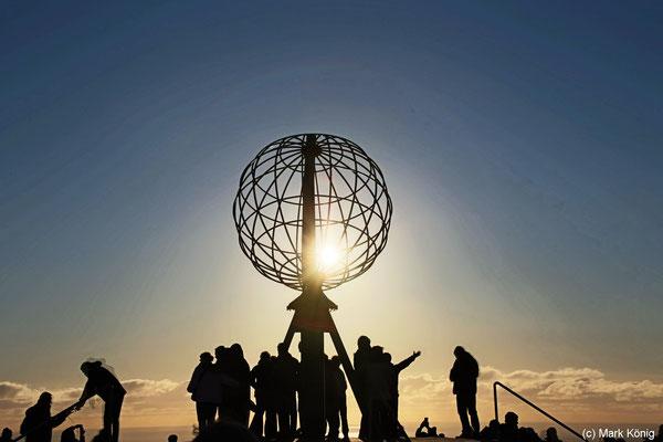 Nordkap: Dunkle Silhouetten von Besuchern am Fuße der bekannten Metallkugel vor der tiefstehenden Mitternachtssonne