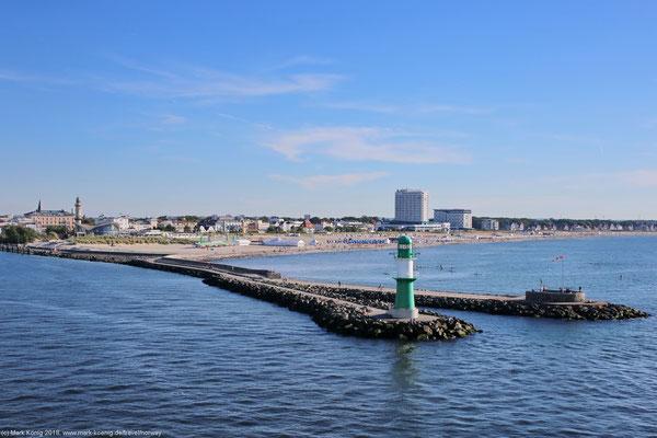 """Hafeneinfahrt von Warnemünde mit Strand und """"Skyline"""" im Hintergrund."""