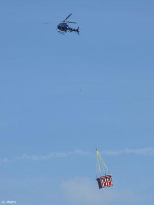 Ein rotes Häuschen wird in Schweden per Helikopter transportiert