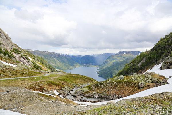 Eine Straße führt den Berg hinunter in ein Tal mit See (Landschaftsroute Ryfylke)