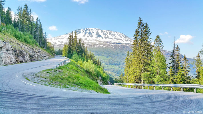 Eine Haarnadel-Kurve ins Tal bietet einen schönen Blick auf den Schnee bedeckten Gaustatoppen in Telemark (Fv651)