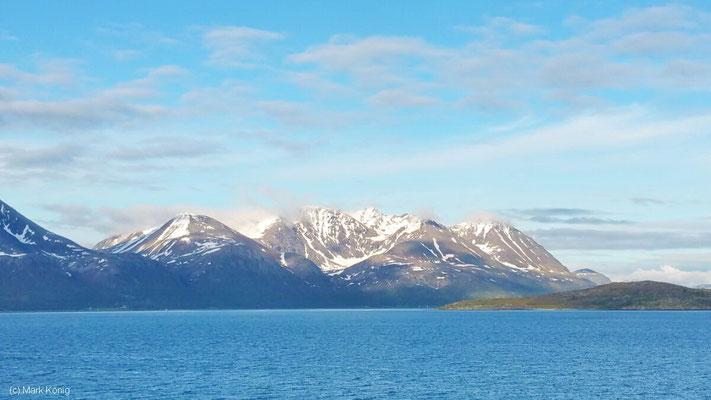 Blick übers Meer auf Schnee bedeckte Berge gibt es von Hurtigruten-Postschiffen sehr häufig