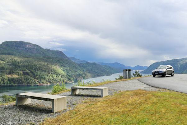 Zwei Mülltonnen und Sitzbänke mit tollem Blick von oben auf einen Fjordarm (Landschaftsroute Ryfylke)