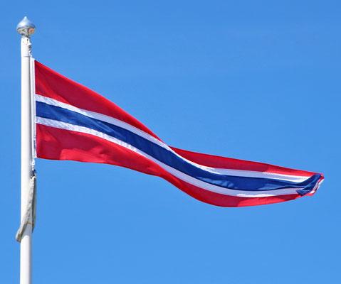 Norwegischer Wimpel weht vor klar-blauem Himmel.