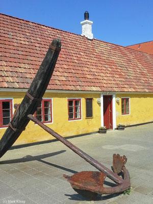 Ein großer rostiger Anker vor dem Gebäude des Hirtshals Kro
