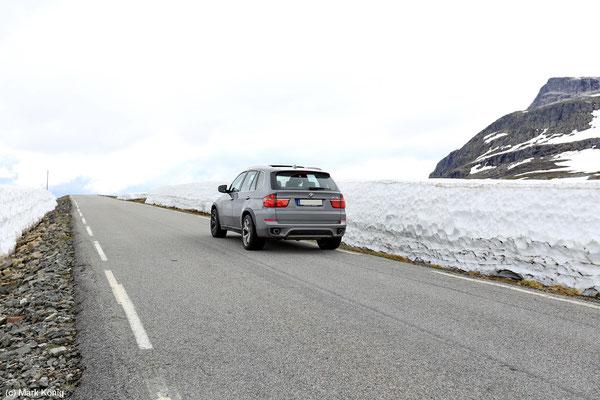 Selbst im Frühsommer liegen manchmal neben Pass-Straßen auf Fjellen noch Schneewände in Höhe eines Autos (hier Landschaftsroute Aurlandsfjellet)