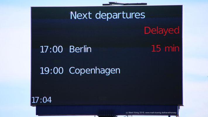 """Eine große digitale Anzeige am Scandlines Fährterminal in Gedser zeigt 15 Minuten Verspätung für die Fähre """"MV Berlin""""."""