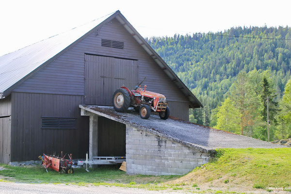 Massey Ferguson 35 tractor on a ramp in front of a barn