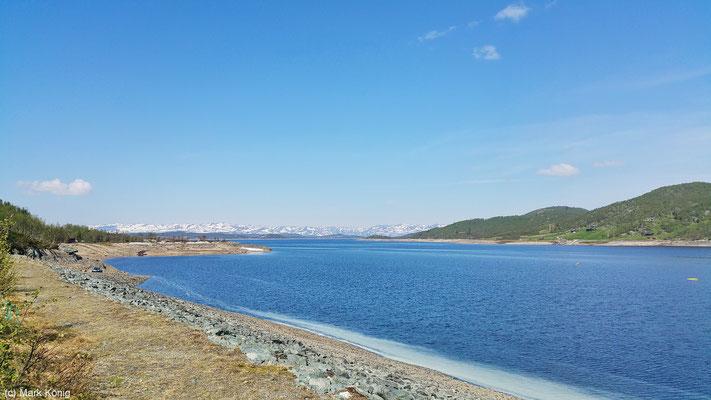 Blick auf den See Møsvatn mit schneebedeckten Bergen im Hintergrund von der Rv37 in der Provinz Telemark