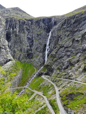 Bei der Felswand am Trollstigen mit großem Wasserfall ermöglichen Sepentinen ein gemächlcihes Vorankommen