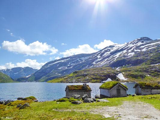 Grasbedeckte Steinhütten an einem Bergsee an der Landschaftsroute Gaularfjellet