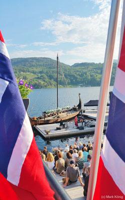 Gäste sitzen am Seeufer von Notodden und hören folkloristische Musik mit Blick auf den blauen See, ein Wikingerschiff und bewaldete Hügel