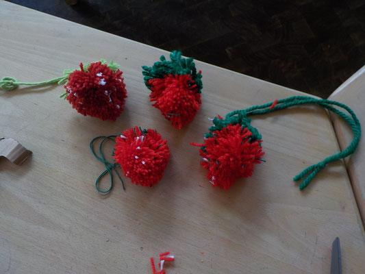 Selbstgebastelte Erdbeer-Pompons aus Wolle.