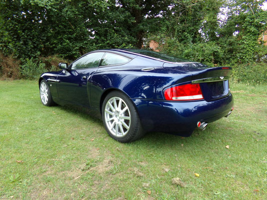 Angled back view of finished body repair work by Precision Paint on a blue Aston Martin Vanquish S