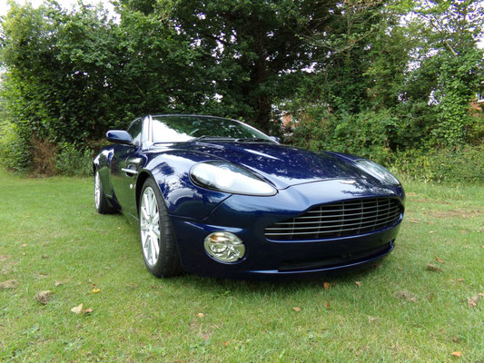 Angled front view of finished body repair work by Precision Paint on a blue Aston Martin Vanquish S