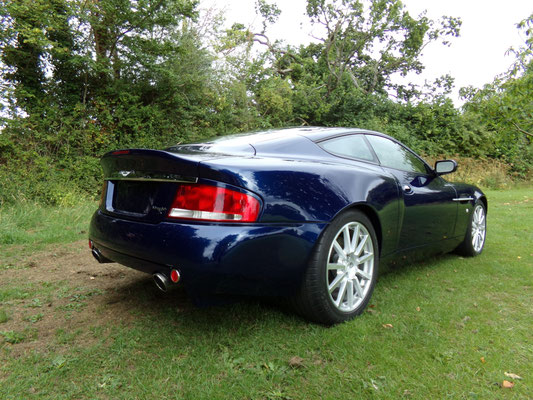 Back view of finished body repair work by Precision Paint on a blue Aston Martin Vanquish S