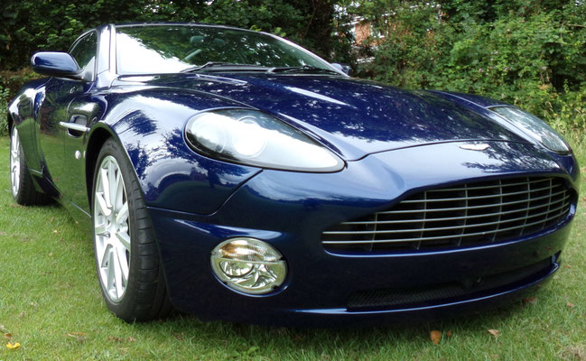 Close-up of finished body repair work by Precision Paint on a blue Aston Martin Vanquish S