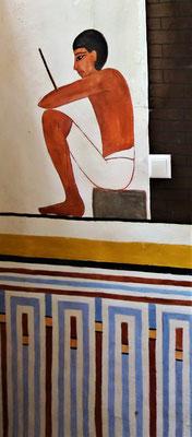 Ein Aufseher macht eine Pause. Hinter ihm befindet sich eine fertige Mauer aus Lehmziegeln. Darunter ist eine Palastfassade zu sehen. Malerei: Daniela Rutica. Foto: Jennifer Peppler
