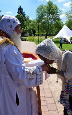 S.E. Bischof Anba Damian verteilt das Heilige Brot. Foto: Jennifer Peppler