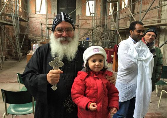 S.E. Bischof Anba Damian mit einer kleinen Teilnehmerin am Abendmahl nach dem Gottesdienst in der neu entstehenden Kirche in Borgentreich