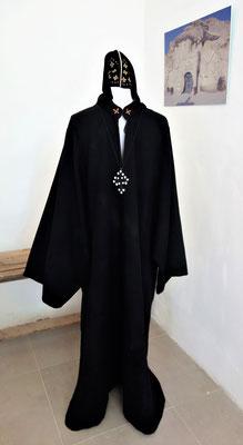 Die schlichte Bekleidung der Koptischen Mönche mit Kopfbedeckung und dem Koptischen Kreuz aus Leder.