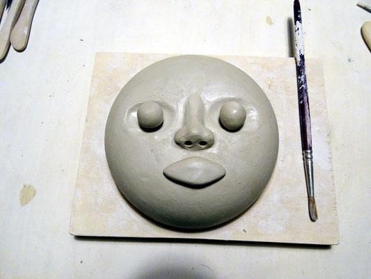 Nasenrücken angleichen und verstreichen, Nasenlöcher bohren. Zwei Kugeln für die Augäpfel formen und locker in die befeuchteten Augenhöhlen einsetzen. Für den Mund ein Tonstück formen und ansetzen.
