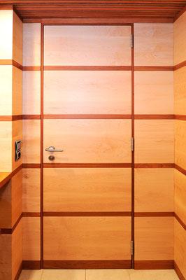Porta interior integrada en els plafons de fusta de la paret